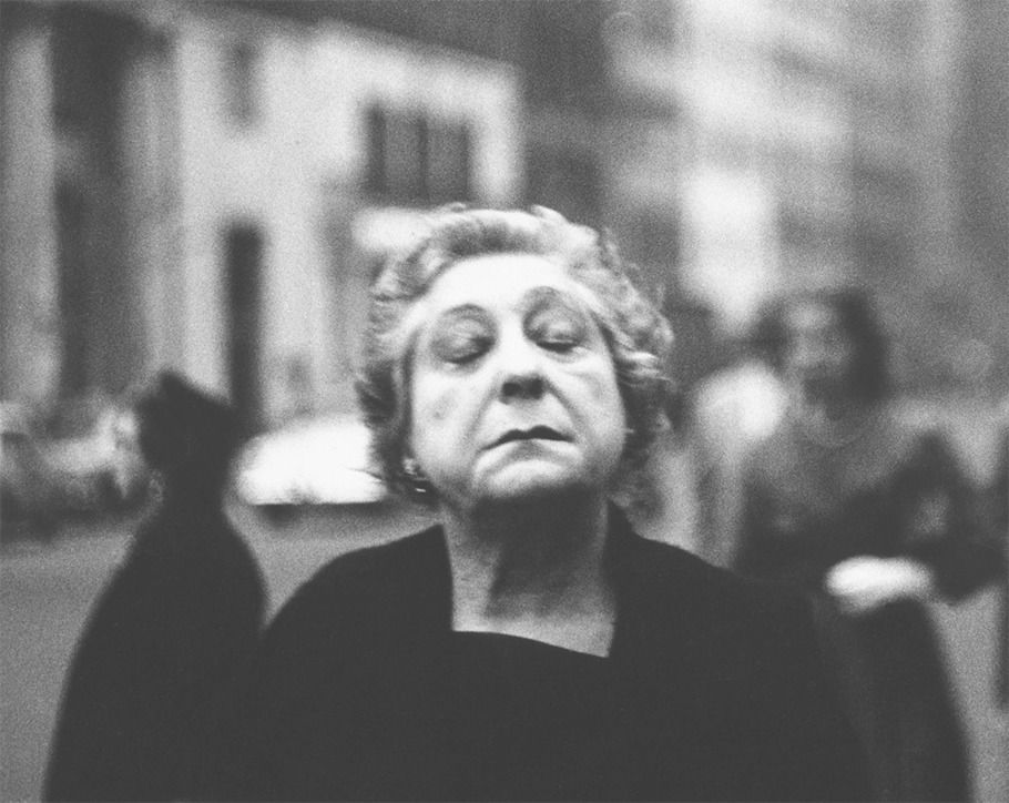 Woman on the street with her eyes closed, 1956.