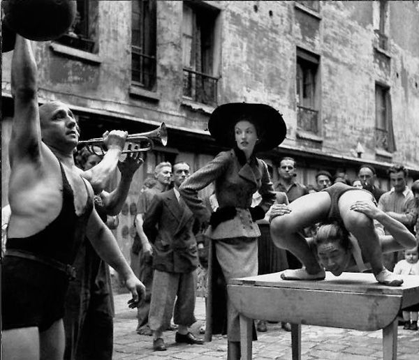 Richard Avedon, Elise Daniels with Street Performers, suit by Balanciaga, Le Marais, Paris, August 1948 © 2015 The Richard Avedon Foundation
