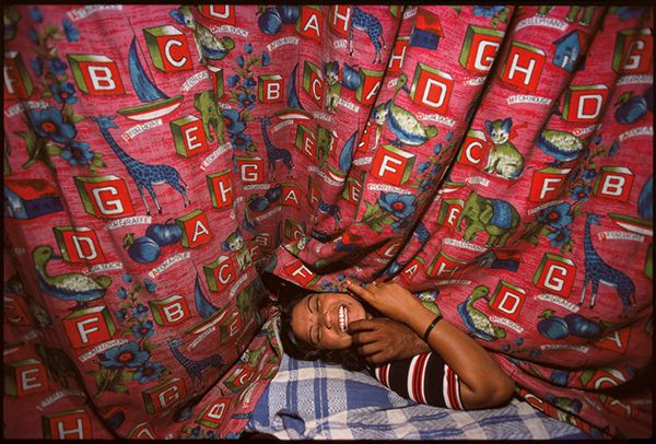 Kamla behind Curtains with a Customer, Falkland Road, Bombay, India, 1978 © Mary Ellen Mark